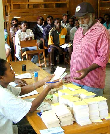 An elderly man receives voting forms during an election in the capital of Vanuatu.