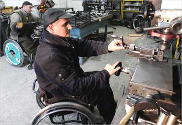 Disabled men work at a wheelchair assembly shop in Tbilisi, Georgia.