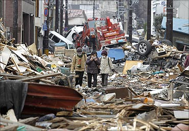 People make their way as they look for their houses among the ruins of the destroyed residential part of Kamaishi