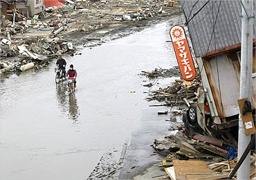 People ride their bicycles in a flooded road at an area destroyed by an earthquake.