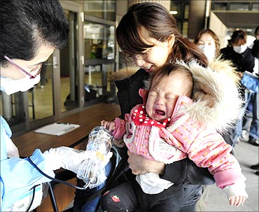A baby and her mother are scanned for radiation before they enter an evacuation centre in Fukushima Prefecture.