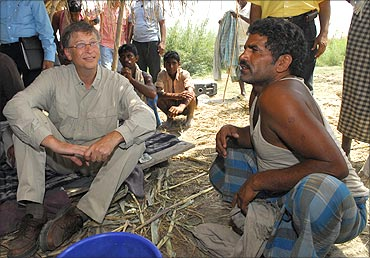 Bill Gates (L) interacts with a villager in Aulali village, in Bihar.