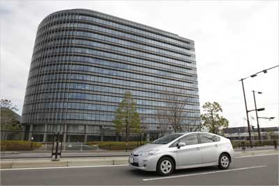 Toyota Motor Corp's Prius hybrid car travels in front of the company headquarters.