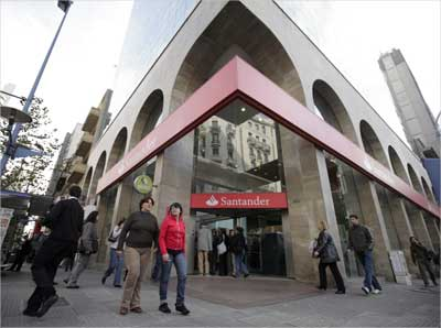 Residents walk in front of a Santander bank branch in downtown Montevideo, Uruguay.