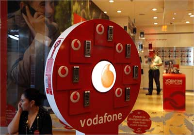 A woman talks on her mobile phone in front of a Vodafone store at Vodafone Turkey headquarters in Istanbul.