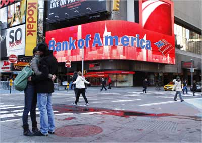 A couple embraces in front of a Bank of America sign on a building in Times Square in New York.