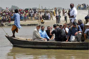 Gates (front 2nd L) sits in a boat as he crosses river Kosi in Bihar.