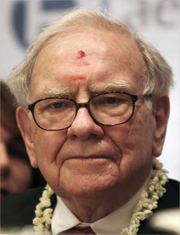 Warren Buffett, wearing a traditional 'tika' pauses during a news conference in Bengaluru.
