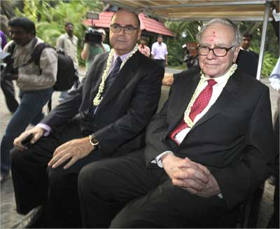Buffett (R) sits in a golf cart with Eitan Wertheimer, chairman of ISCAR Metalworking.