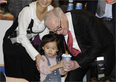 Buffett gives a cup of DQ ice cream to a Chinese girl during his visit to a new Dairy Queen store in Beijing.