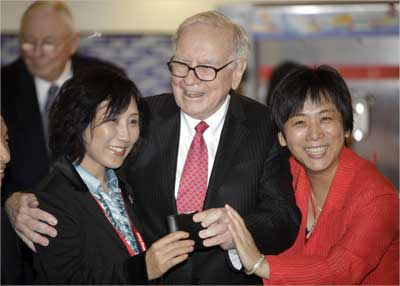 Buffett (C) takes out his wallet to pose for a photo during his visit a new Dairy Queen store in Beijing.