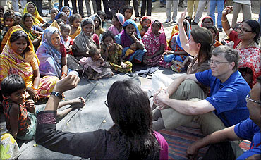 Bill Gates and his wife Melinda interact with slum dwellers during their visit to a slum area in Danapur, Bihar.