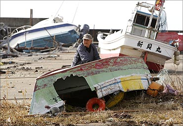 Fisherman Ryusuke Isogai in front of his ship (R) , which was washed onto the shore.
