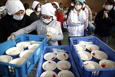 Volunteers prepare food to be distributed to victims at a shelter.