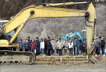 Family members of victims of the earthquake and tsunami watch as an excavator digs a mass grave.