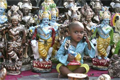 The son of an idol vendor plays with a mobile phone.
