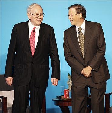 Bill Gates (R) talks to Warren Buffett.