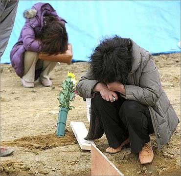 Survivors grieve at a grave of a victim of the March 11 earthquake at a mass grave.
