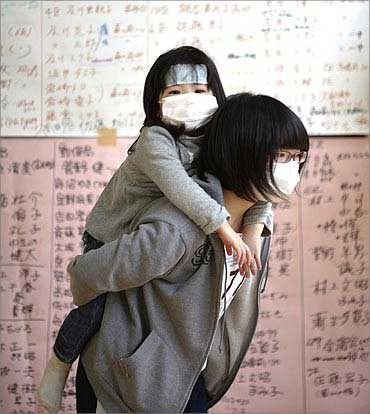 Owada Yuna carries her three-year-old sister Yumeka as she searches for names missing friends.