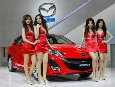 Models pose beside a Mazda 3 during the 32nd Bangkok International Motor Show in