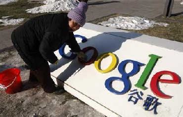 A woman cleans the logo of Google China outside the company headquarters in Beijing