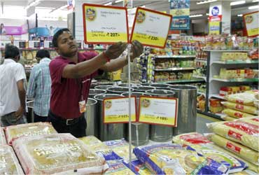 A staff of a food superstore arranges price tags.