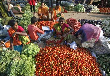 Vendors sell vegetables at an open air fruit and vegetable market.