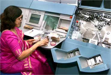 A RBI employee counts currency notes before placing them into new machines.