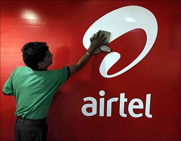 A worker cleans a Bharti Airtel logo.