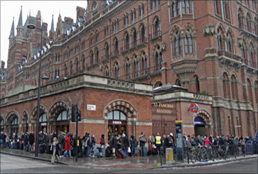 Eurostar passengers queue outside the terminal for trains at St Pancras station in London.