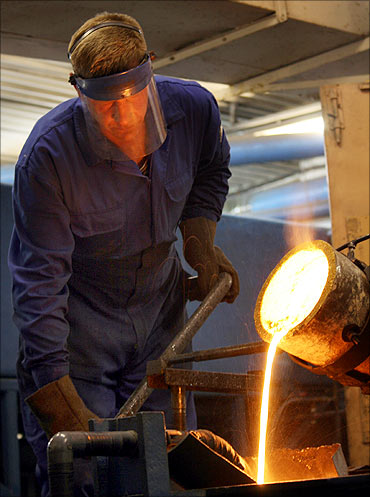 A worker casts an ingot of gold at Kolyma Refinery in the village of Khasyn, Russia.