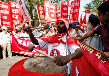 A CPI-M activist beats a drum at a rally against rising prices.