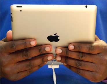 A staff member holds the Apple iPad2 at the Apple store in London.