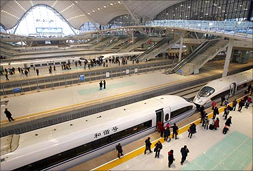 Travellers board a high-speed train which heads to Guangzhou in Wuhan.