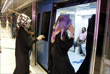 Women walk into a train after the official opening of the Gulf Emirate's first metro network.