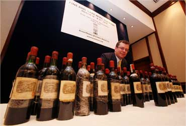 Acker Merrall's president John Kapon poses with a lot of 70 Chateau Lafite Rothschild bottle.