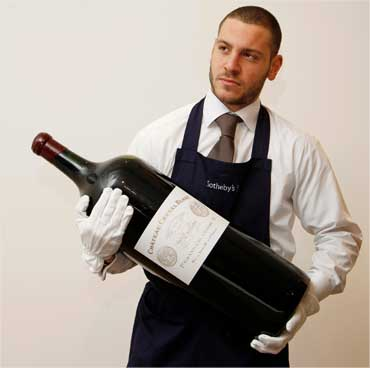 An employee poses with an 18 litre melchior of Chateau Cheval Blanc.