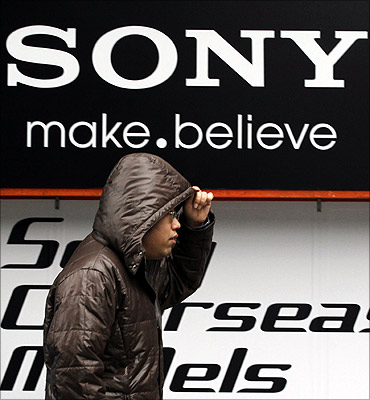 A man walks past a Sony logo in front of an electronic shop.
