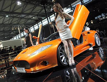 Models pose next to a Spyker C8 Aileron during the Shanghai Auto Show.