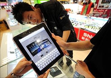 A shop assistant (L) displays an iPad at an electronic products store in Hefei.