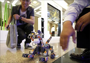 A man looks at a demonstration of a prototype of a dog robot during the 2011 IEEE conference.