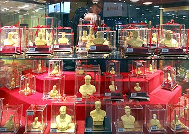 A vendor places a gold statue featuring late Chinese leader Mao Zedong at a gold store in Xiangtan.