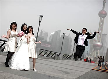 A wedding party pose for pictures with the Oriental Pearl TV Tower in the background.