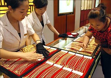 A customer selects gold jewellery from a glass case at a jewellery shop in Huaibei.