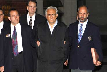 Dominique Strauss-Kahn (C) being escorted from a New York Police Department unit.