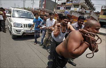 Supporters of Bharatiya Janata Party pull a vehicle with ropes.