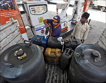A worker fills plastic containers with diesel at a fuel station in Kolkata.