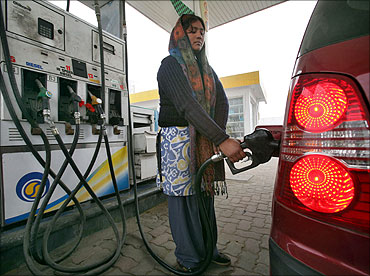 An employee fills a vehicle with petrol at a fuel station in Jammu.