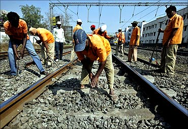 Employees of the Indian railways work on railway tracks.