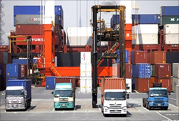 Containers are unloaded from a truck for export at Yokohama port in Yokohama.